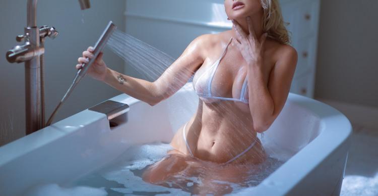 Білявка приймає ванну в купальнику