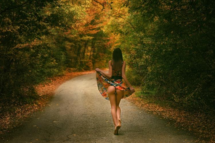 Дівчина гуляє по осінньої дорозі
