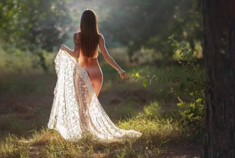 Гола дівчина гуляє по лісу