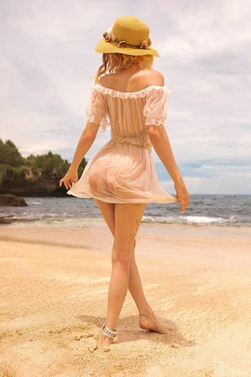 Дівчина в прозорій сукні гуляє по пляжу